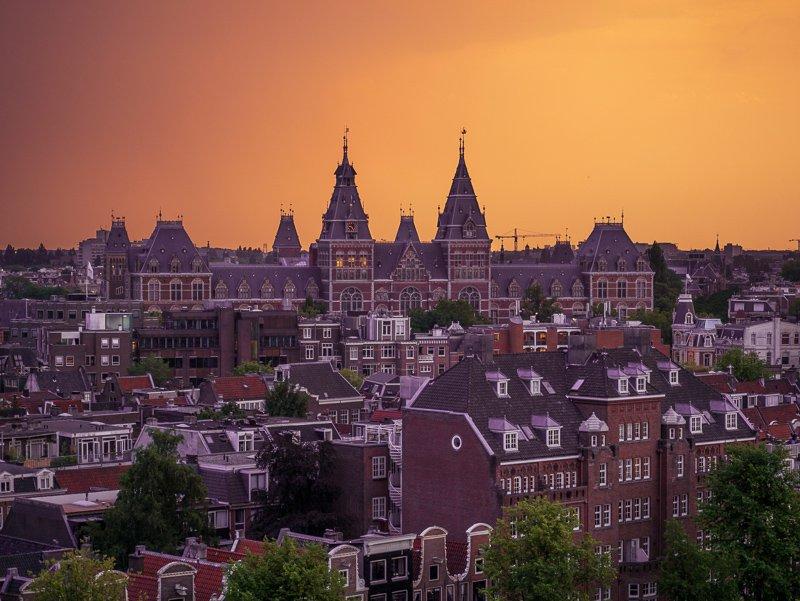 Doe een drankje op een dakterras tijdens zonsondergang. Iets wat je niet mag missen tijdens een weekend in Amsterdam.