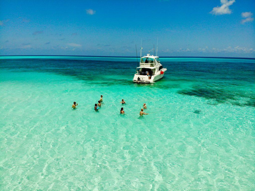 Een catamaran in helderblauw water met zwemmende mensen