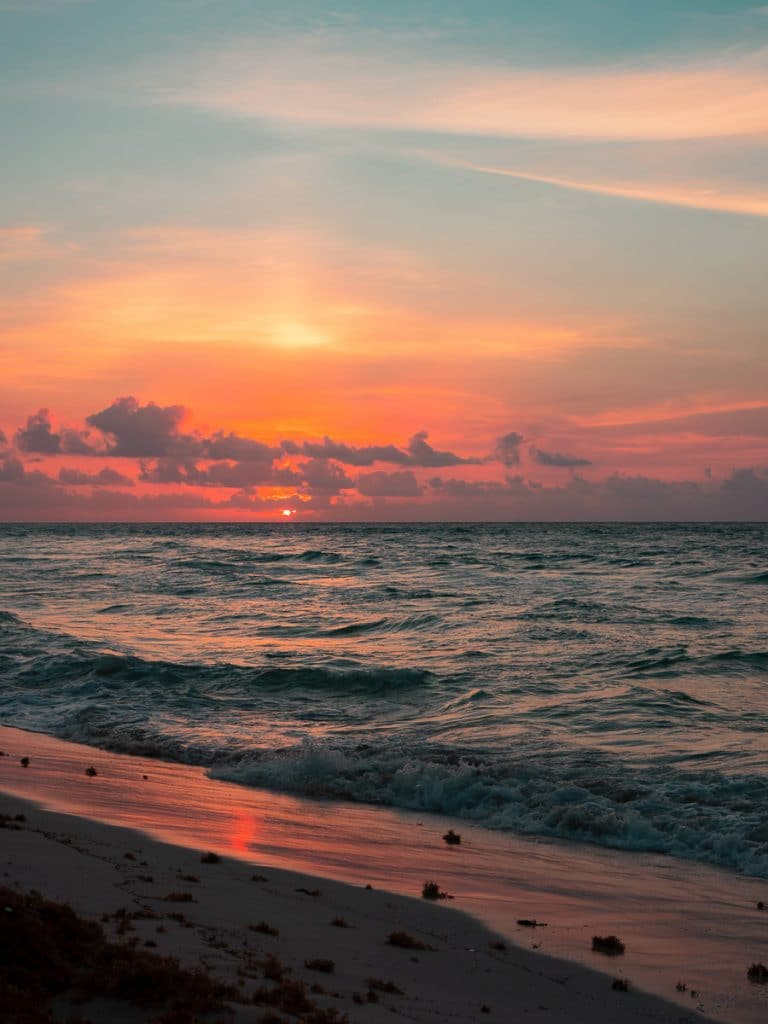 Een oranje lucht en een ondergaande zon in de zee van Playa del Carmen in Mexico