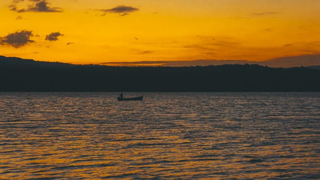 Een oranje lucht en een bootje tijdens een zonsondergang in Nicaragua