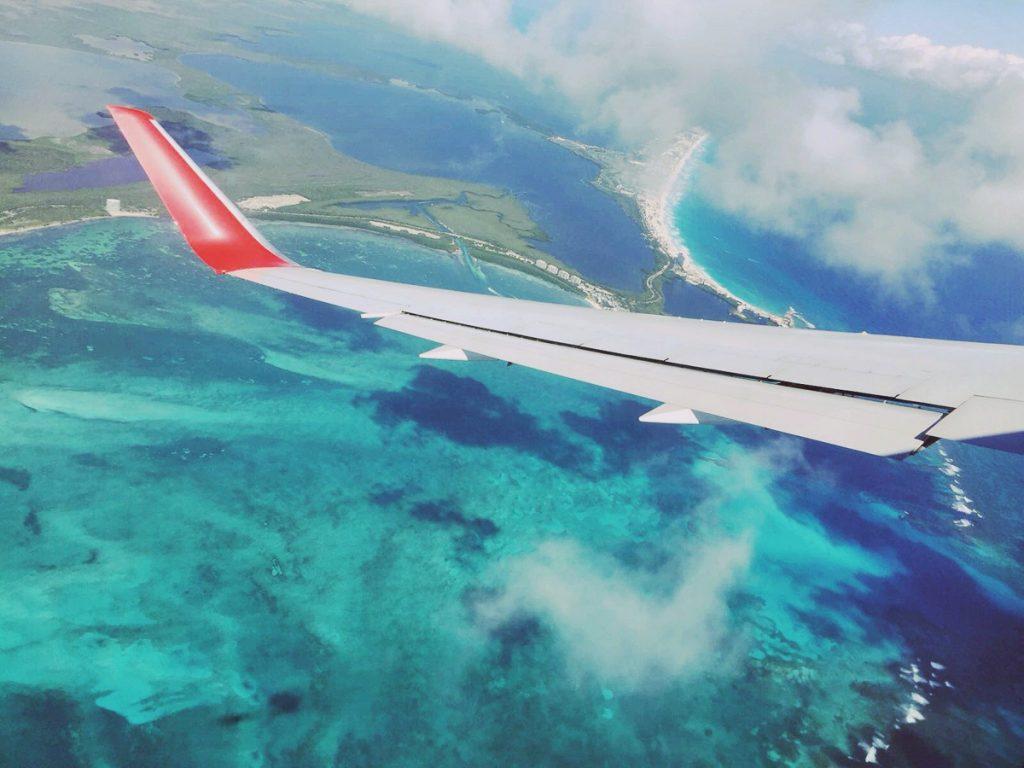 Vleugel van het vliegtuig over de felblauwe zee van Zuid-Mexico