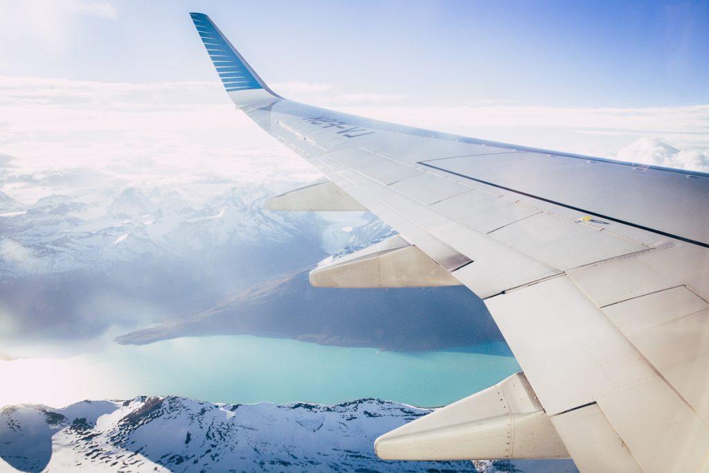 Vliegen boven besneeuwde bergpieken en een blauw meer