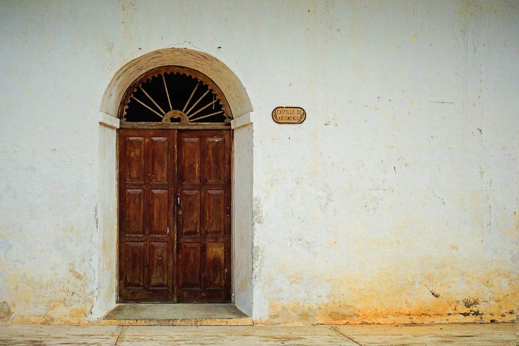 Een bruine deur en een witte muur op een oud koloniaal pand