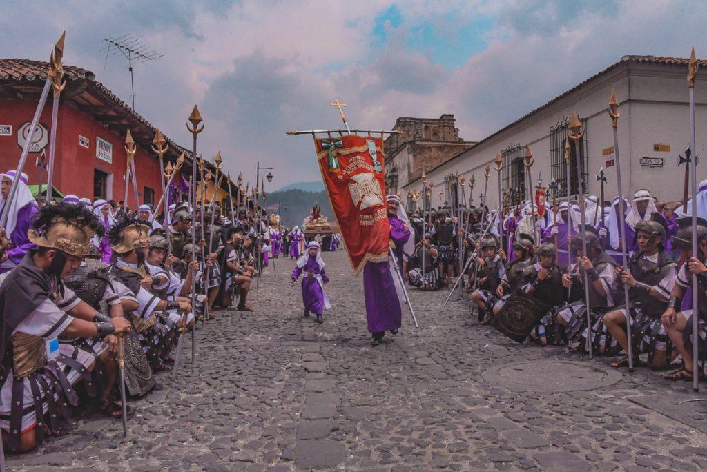 Veel mensen in een paars gewaad in een straat vol kinderkopjes tijdens een evenement in Antigua in Guatemala