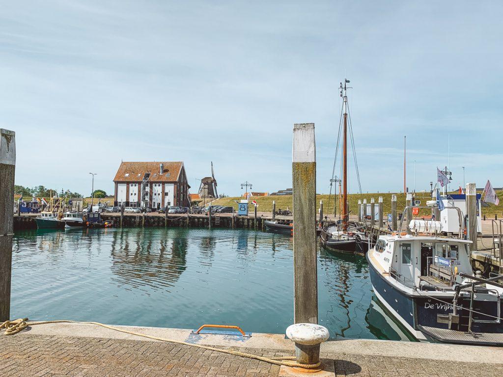 De haven met bootjes en een molen op de achtergrond van Oudeschilde op Texel