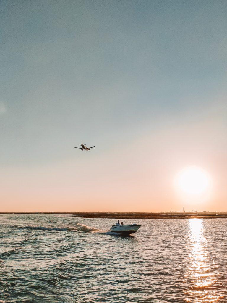 Boot en een overvliegend vliegtuig tijdens een zonsondergang in Faro in Portugal