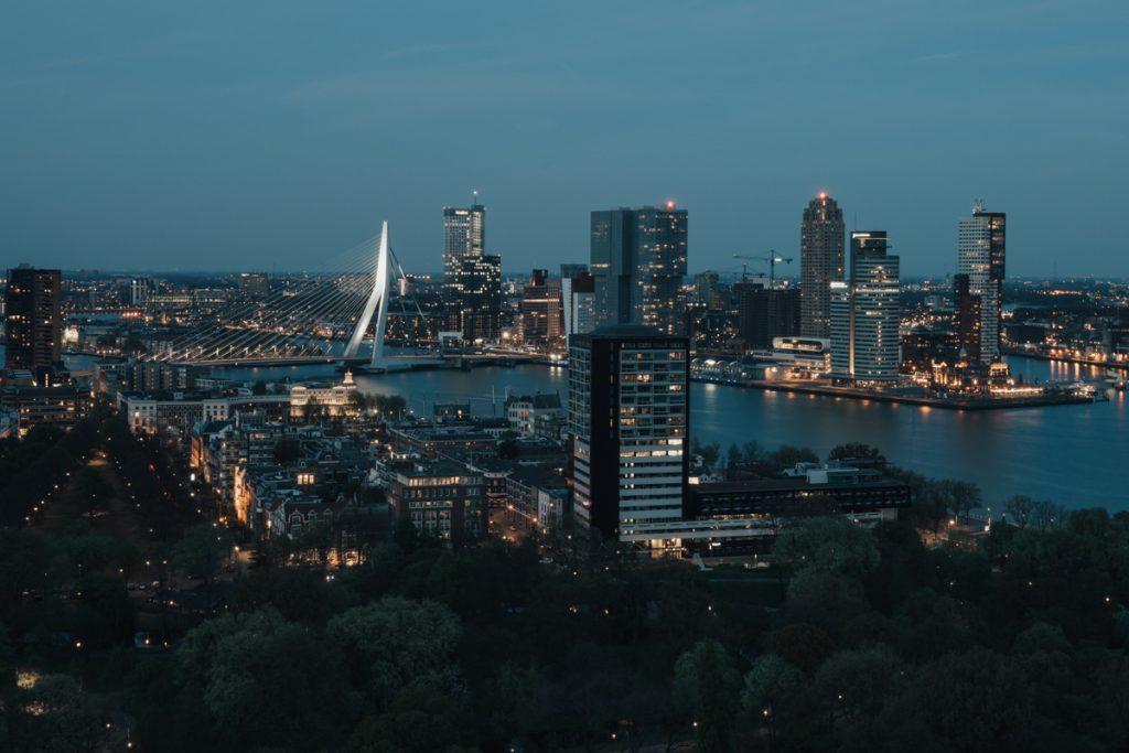 Uitzicht vanaf een dakterras, met de knipperende lichten van de wolkenkrabbers en de Erasmusbrug op de achtergrond