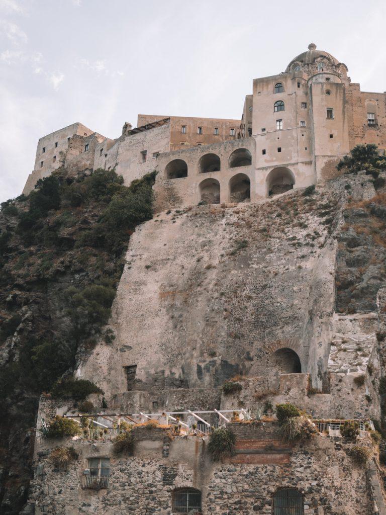 De zandkleurige Castello Aragonese bovenop een rots