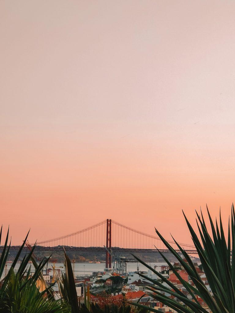 Uitzicht op Ponte 25 de Abril met een oranje lucht, een van de bezienswaardigheden van Lissabon