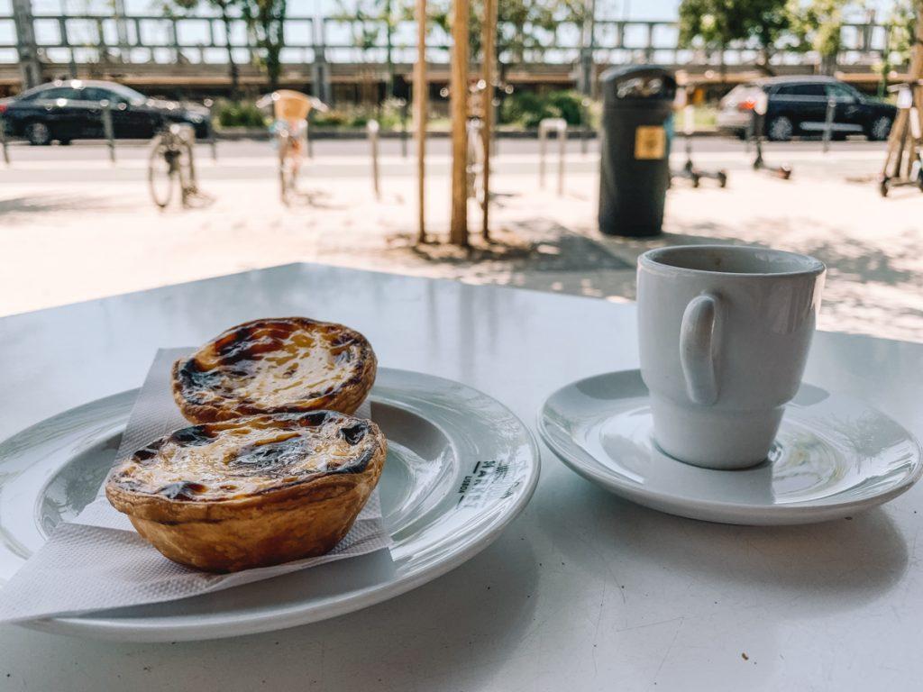 Twee pastel de nata's en koffie op een terras