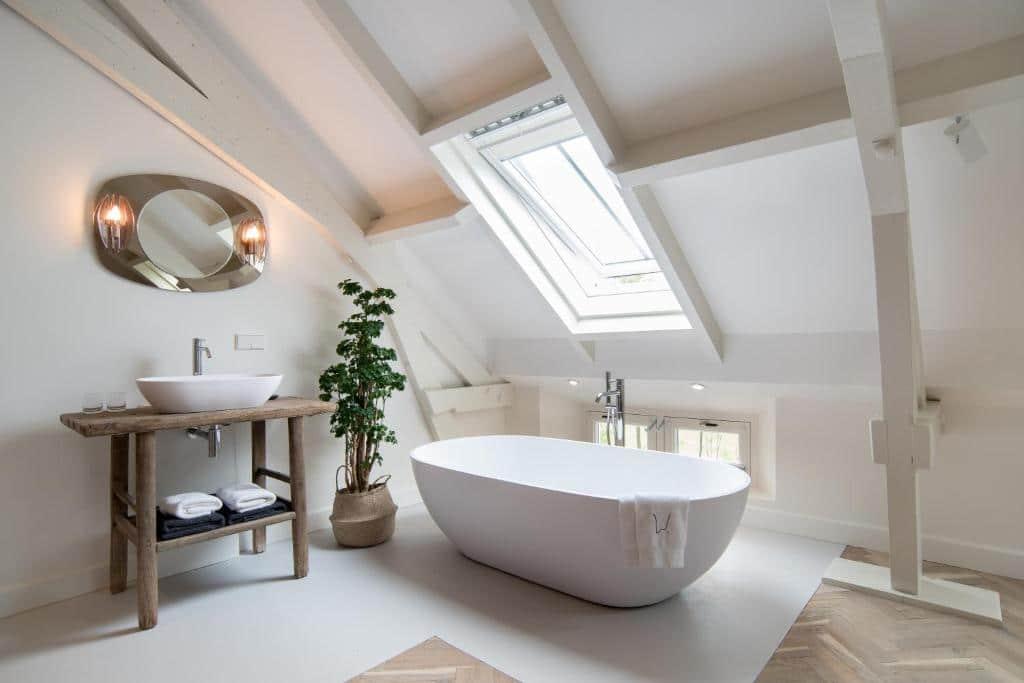De witte hotelkamer met losstaand bad van Hotel de Witte Dame in Abcoude, een van de leukste hotels in Nederland