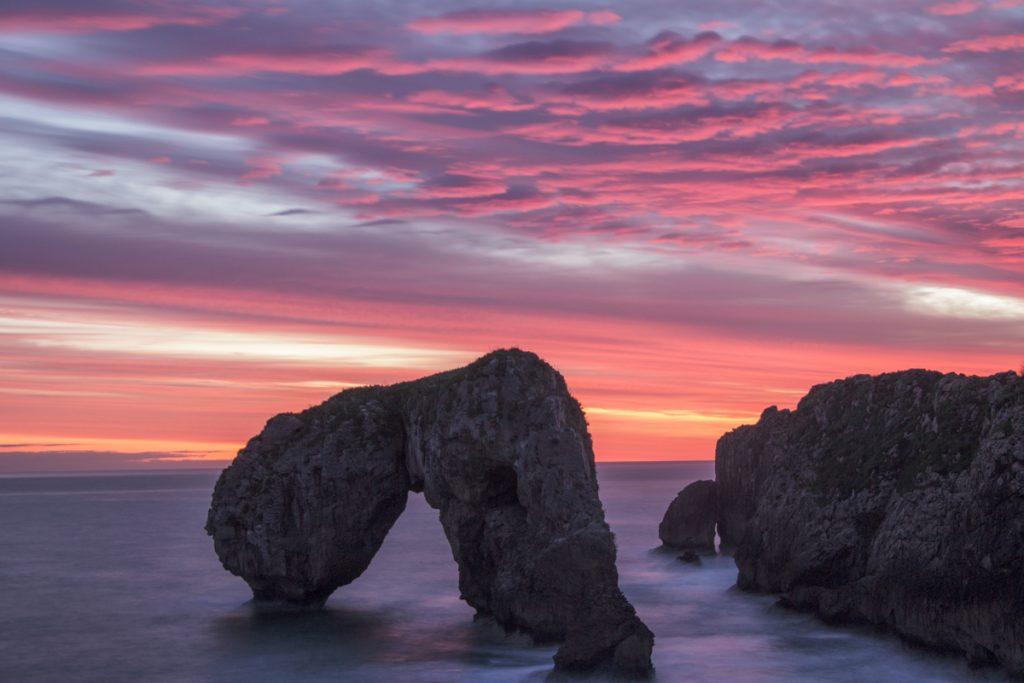 Roze lucht en rotsformaties in zee bij Asturias in Spanje