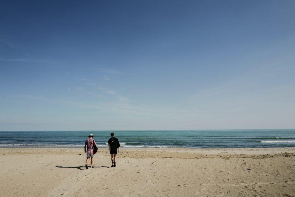 Twee mannen lopend op het strand richting het water bij Lido di Spina