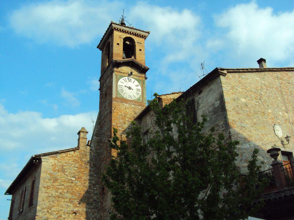 Een kerktoren met klok en boom in Arezzo in Italië