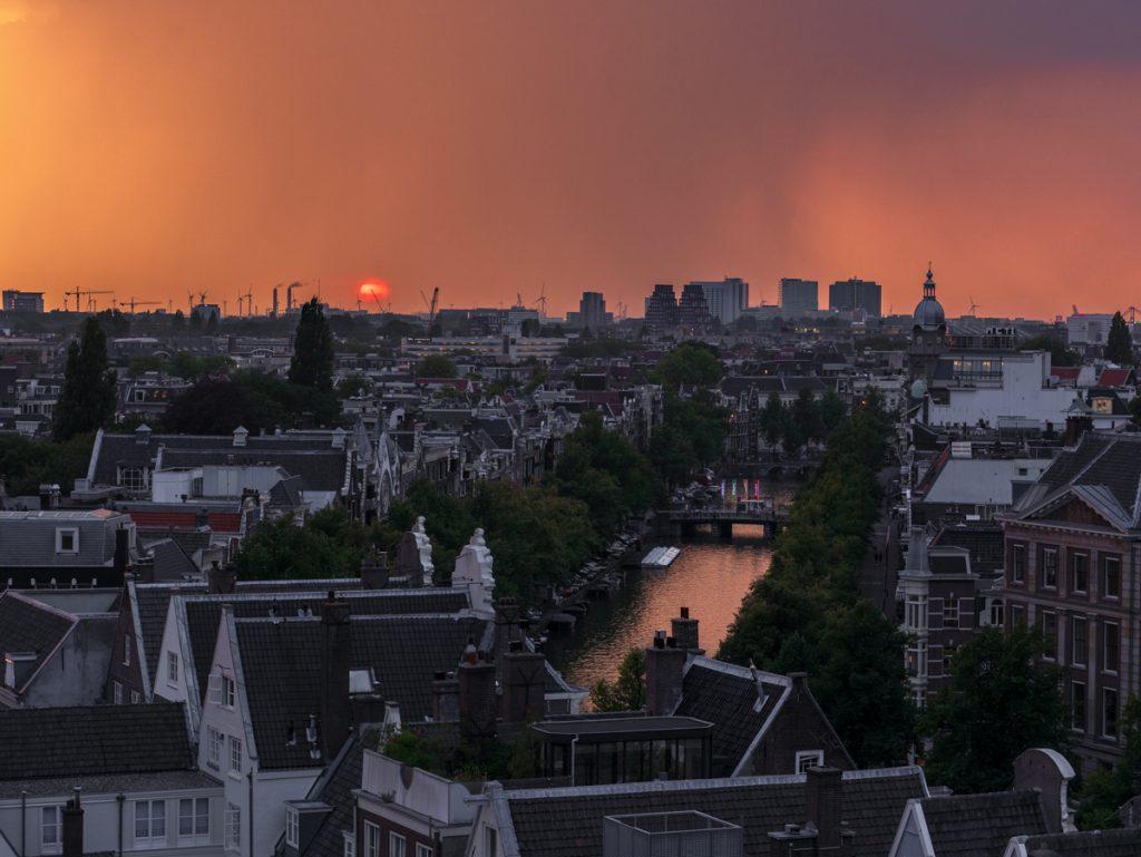 Uitzicht vanaf een dakterras op Amsterdam tijden de zonsondergang