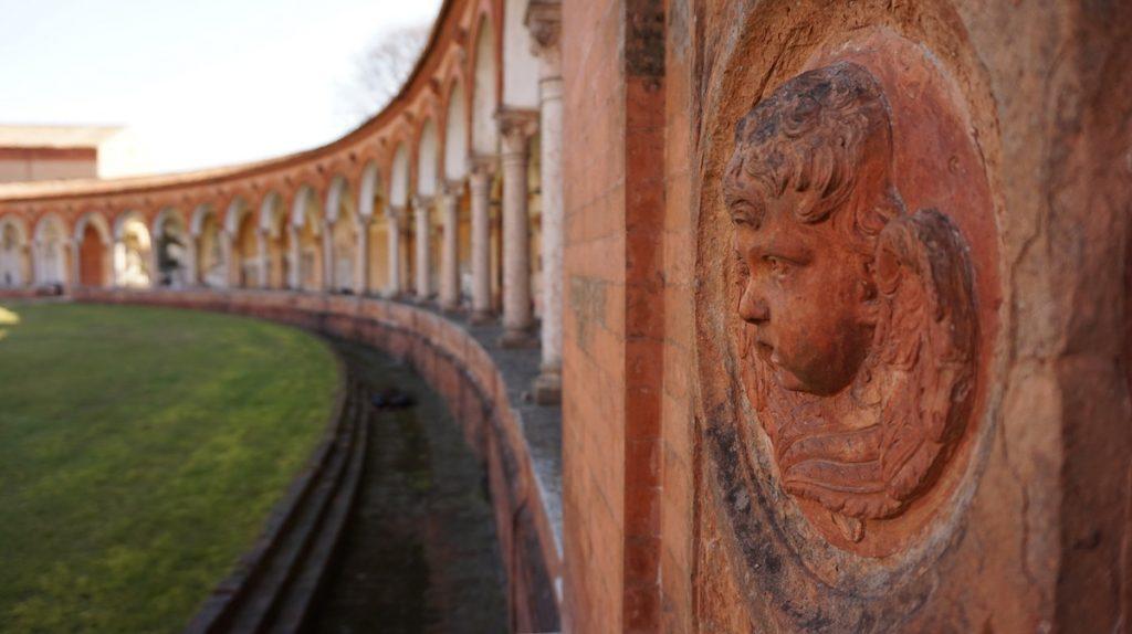 Rode zuilen met beelden van gezichten bij de begraafplaats van Ferraro in Italië