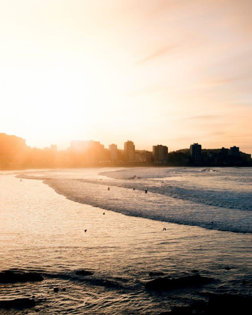 Oranje lucht en onderzakkende zon in de zee bij Gijon in Asturias