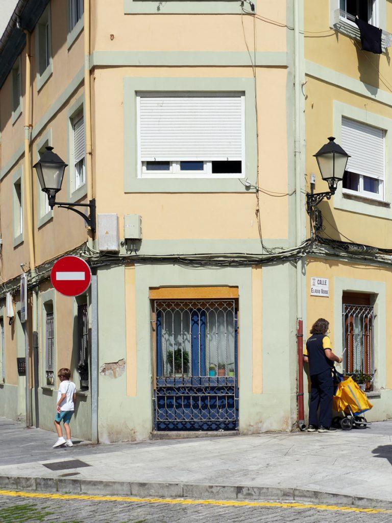 Geel huis met twee mensen op straat in Gijon
