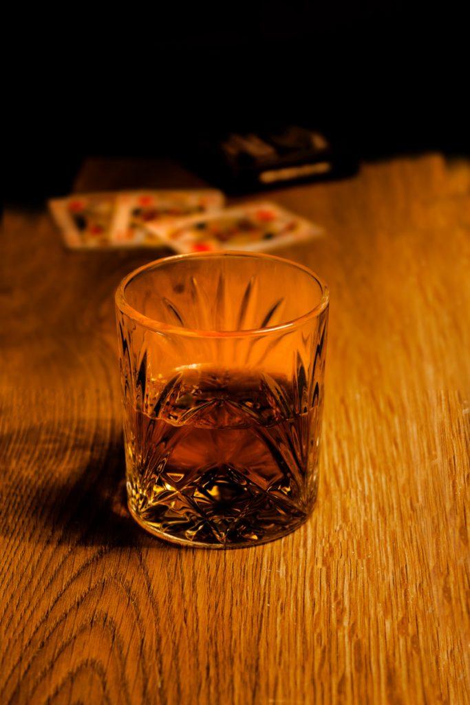 Een glas whisky en potje kaarten op tafel