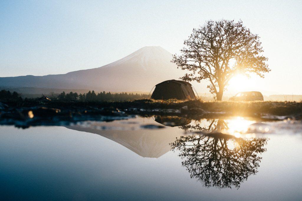 Reflectie van een boom, auto en Mount Fuji in het water tijdens zonsopgang