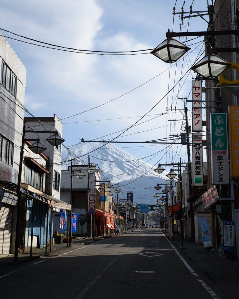 Een geasfalteerde weg in Japan met een besneeuwde Mount Fuji op de achtergrond