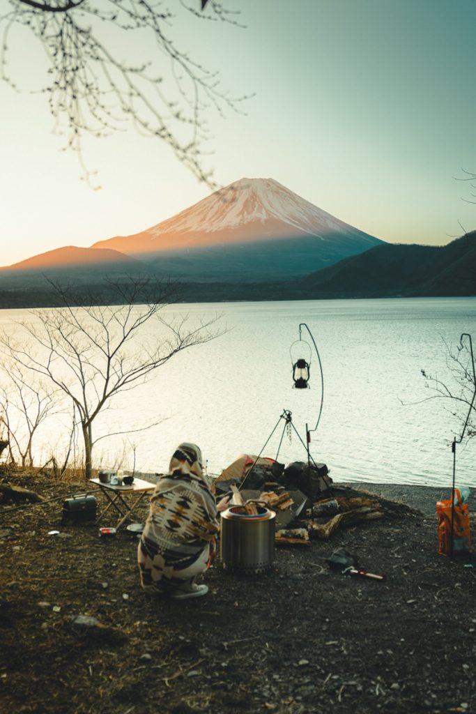 Koken op een gaststelletje tijdens het kamperen, aan het water met Mount Fuji op de achtergrond in Japan