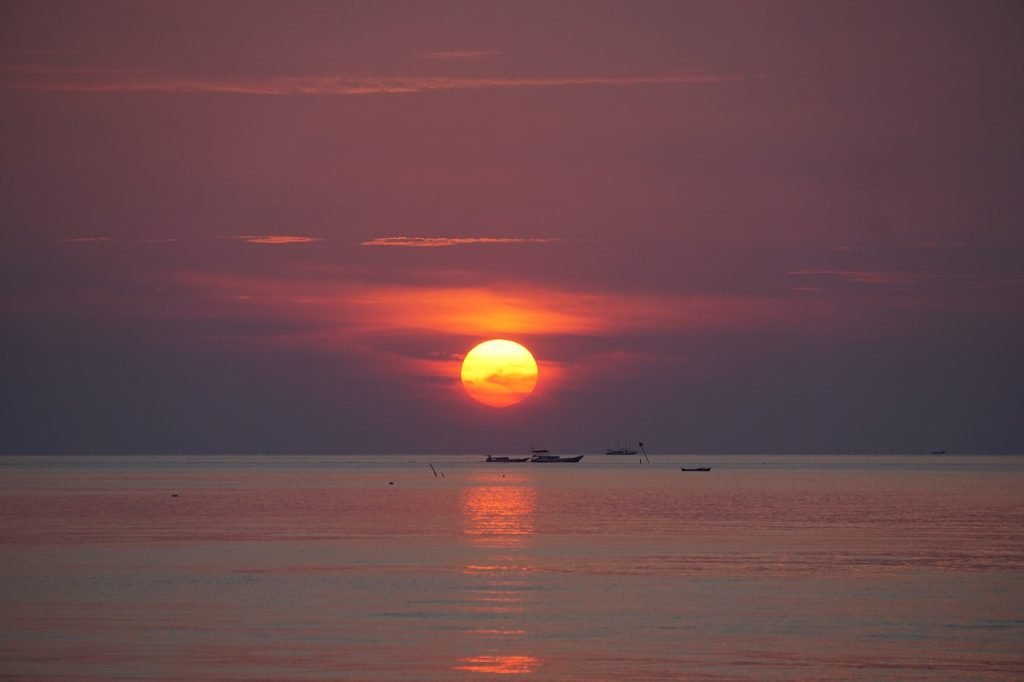 Rode ondergaande zon achter de horizon van de zee
