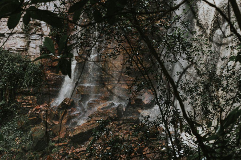 Een waterval tussen de takken en bruine rotsen