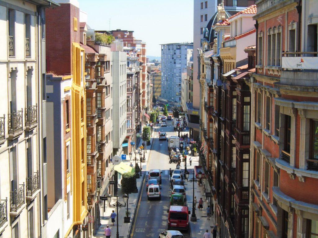 Drukke straat met kleurrijke huizen en auto's op de weg in Oviedo