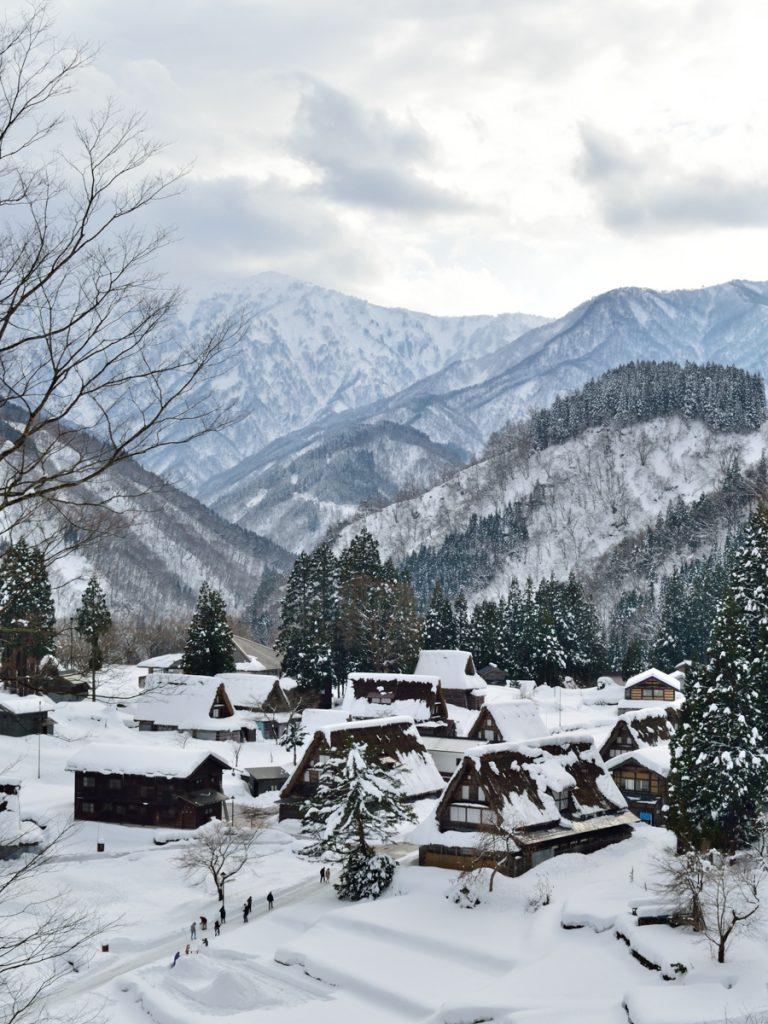 Een besneeuwd bergdorpje in Japan, met bergen op de achtergrond