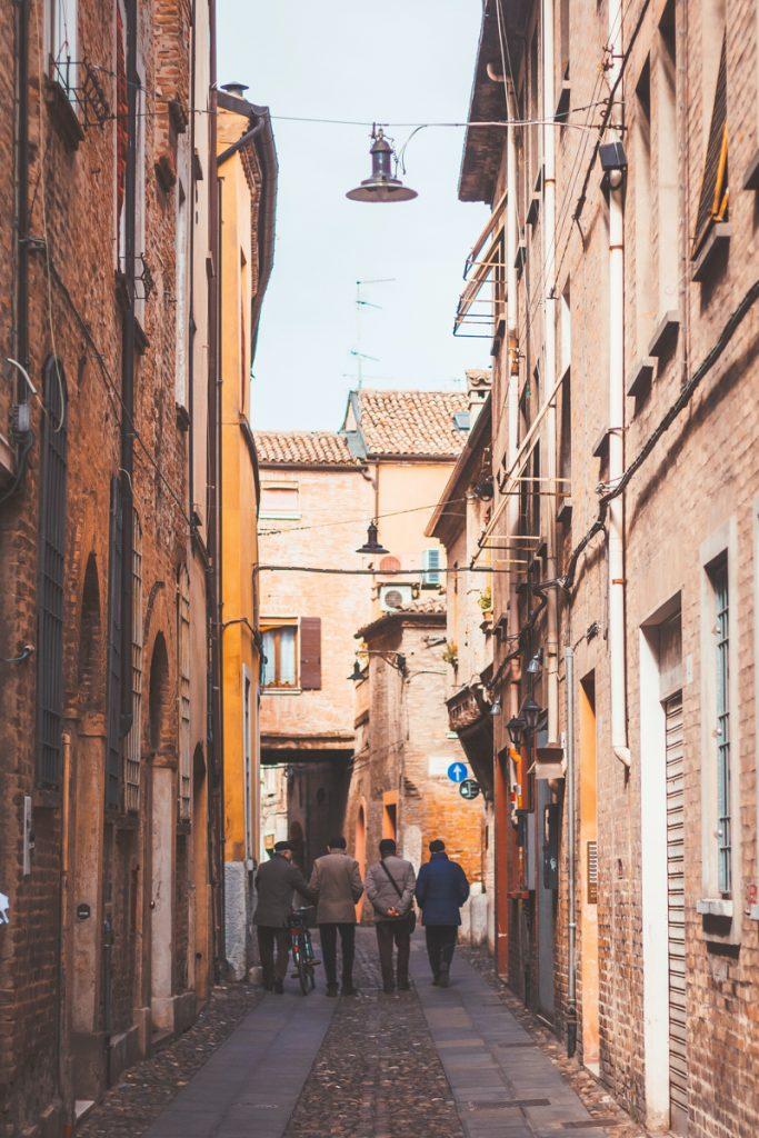 Een gezellig steegje met kleurrijke bloemen en lopende mensen in Ferrara in het noorden van Italië