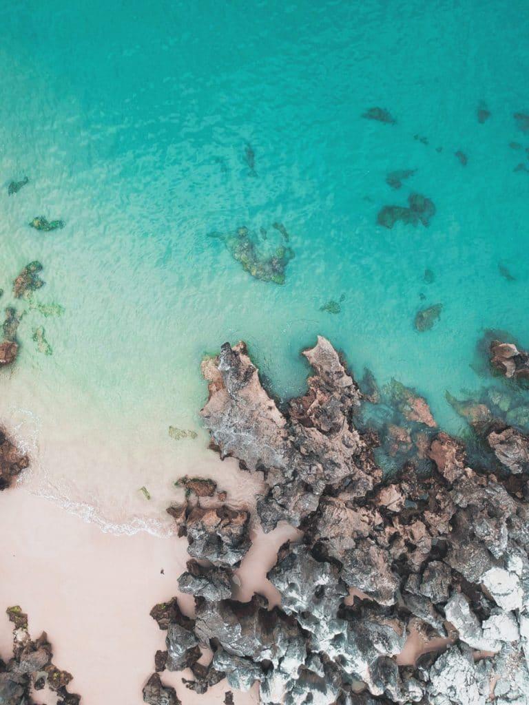 Een dropshot van een azuurblauwe zee met wit strand en wat rotsen bij Asturias in Spanje