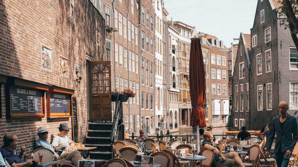 Zonnig terras met mensen die aan het borrelen zijn in Amsterdam