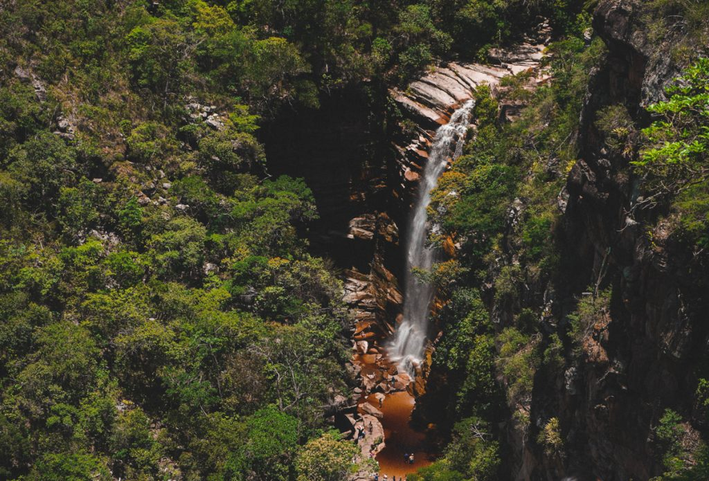 Een waterval dat via bruine rotsen naar beneden stort in een groene omgeving vol bomen