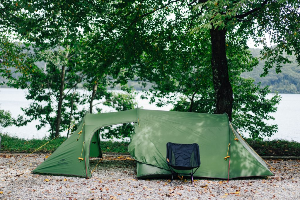 Groene tent naast het water en een boom