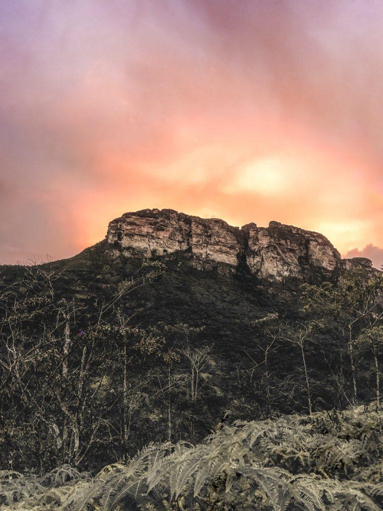 Geel met roze en oranje lucht boven een berg