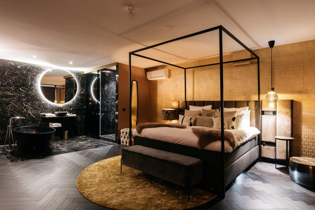 De luxe hotelkamer van Britannique met vrijstaand bad en een marmeren muur