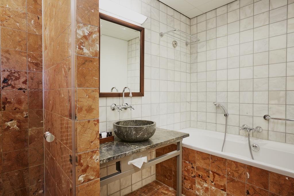 De badkamer met steen en natuurlijke materialen