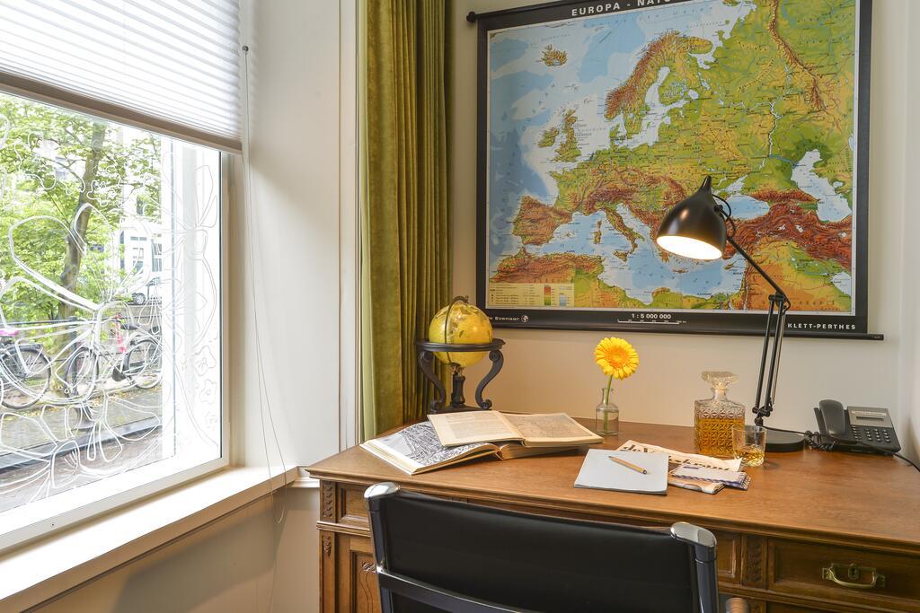 Wereldkaart aan de muur met bureau, met uitzicht op de gracht