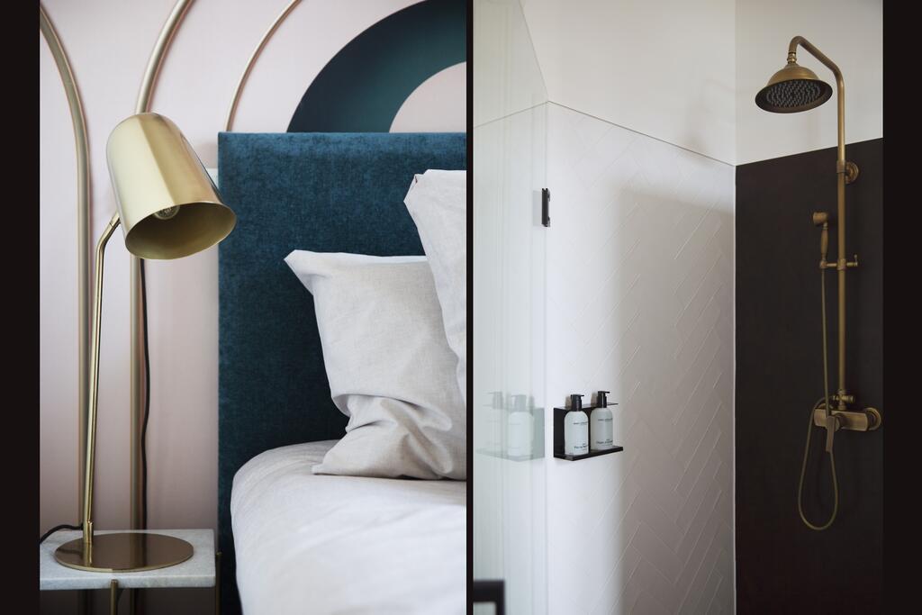De slaapkamer en badkamer met gouden lamp en gouden douchekop van het MUZE Hotel in Utrecht