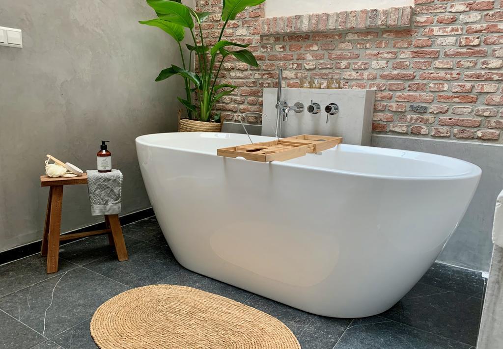 Een prachtige badkamer met vrijstaand bad en een stenen muur