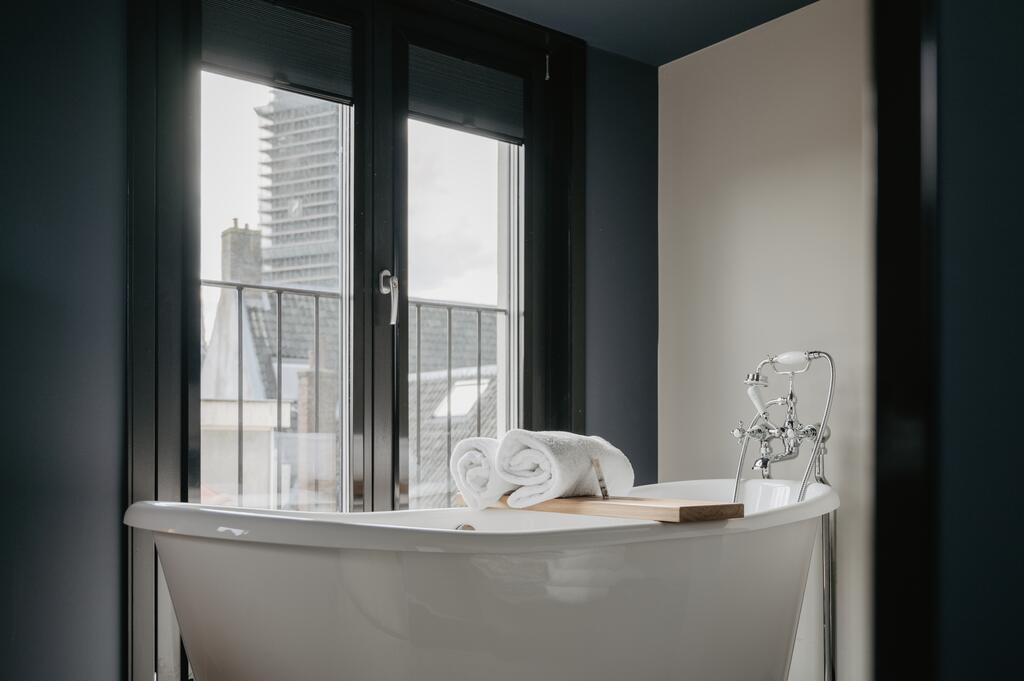 Vrijstaande bad met uitzicht op de stad van het Nox Hotel
