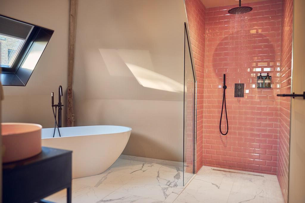Een vrijstaand bad en een roze badkamer van The Anthony