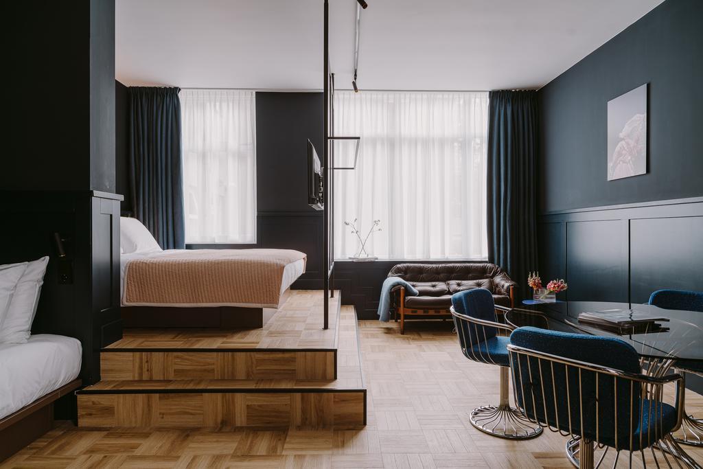 Het bed op een verhoging en een zitgedeelte in een van de kamers van het Supernova Hotel