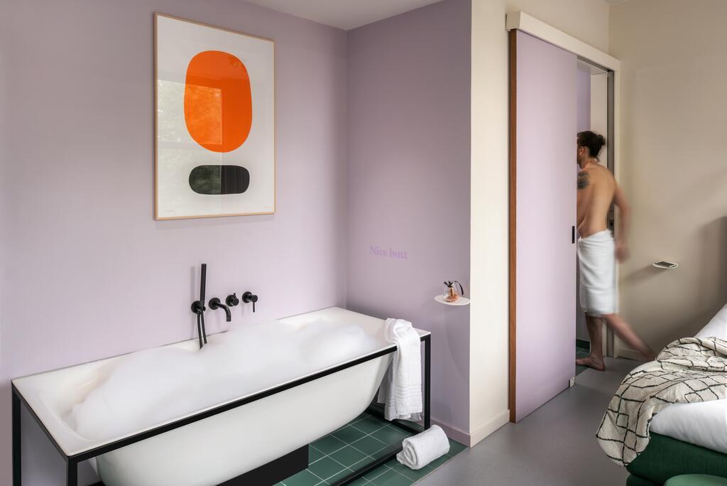 Het vrijstaande bad tegen de roze muur en groene tegels van Hotel Unplugged, een van de mooiste hotels in Rotterdam