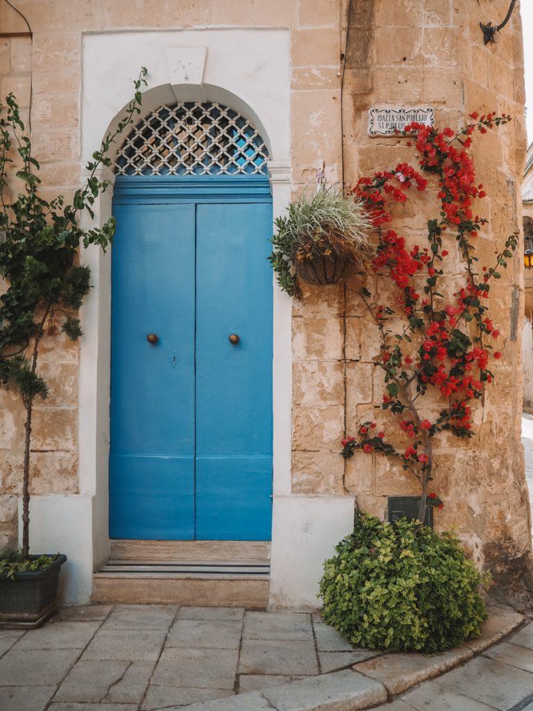 Een blauwe deur en rode rozen in de Mdina